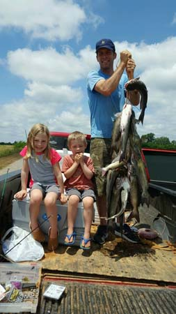 father with two daughters and string of fish